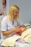 Blonde d'exposition d'International d'Intercharm XXI la jeune belle dans un manteau blanc fait orner-rajeunir des traitements Photo stock