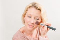Blonde Dame Applying Make-Up auf Backe Lizenzfreies Stockfoto
