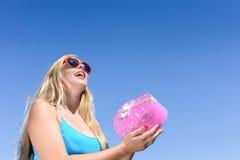 Blonde Dame der Junge recht in der Sonnenbrille, die Rosa hält Lizenzfreies Stockbild