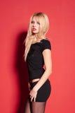 Blonde Dame in der schwarzen Aufstellung auf Rot Lizenzfreies Stockbild