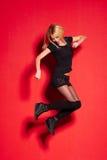 Blonde Dame in der schwarzen Aufstellung auf Rot Lizenzfreies Stockfoto