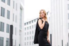 Blonde Dame in der schwarzen Bluse und im Rock, die nahes Büro steht Lizenzfreies Stockfoto