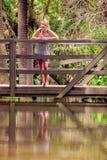 Blonde Dame, die über einer Brücke sich lehnt Lizenzfreies Stockfoto