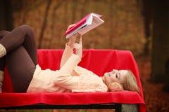 Blonde Dame, die auf Bank liegt Lizenzfreie Stockbilder