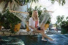 Blonde Dame, die auf einer Hängematte stillsteht Lizenzfreie Stockfotografie