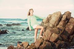 Blonde Dame, die auf Felsen im Ozean steht Stockbild