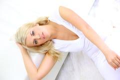 Blonde Dame, die in ein Schlafzimmer legt Lizenzfreie Stockfotos