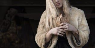 Blonde Dame, die ein trockenes Blatt hält Stockbild