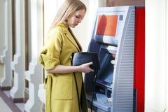 Blonde Dame, die einen Geldautomaten verwendet Lizenzfreies Stockfoto