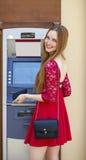 Blonde Dame, die einen Geldautomaten verwendet Stockfotografie