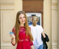 Blonde Dame, die einen Geldautomaten verwendet Stockfotos