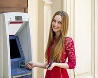 Blonde Dame, die einen Geldautomaten verwendet Stockfoto