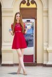 Blonde Dame, die einen Geldautomaten verwendet Stockbilder