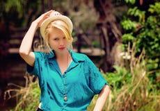 Blonde Dame, die einen Hut hält Lizenzfreie Stockbilder