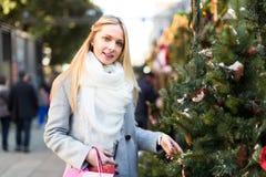 Blonde Dame, die einen Weihnachtsbaum kauft Stockfotos