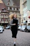 Blonde Dame, die entlang Straße läuft Stockfotos