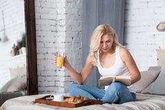 Blonde Dame, die Frühstück und Lesebuch hat Stockfoto