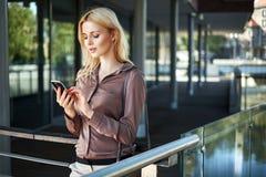Blonde Dame, die ihren Smartphone verwendet Stockfotos