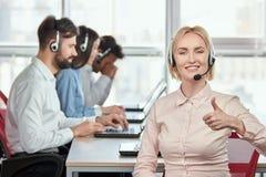 Blonde Dame, die im Büro sich zeigt Daumen arbeitet Lizenzfreie Stockfotos