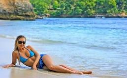 Blonde Dame, die im Wasser auf dem Strand liegt Lizenzfreies Stockbild