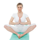 Blonde Dame, die im Weiß meditiert Lizenzfreie Stockbilder