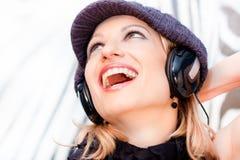Blonde Dame, die Musik hört Stockbilder