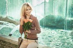 Blonde Dame, die nahe bei dem Brunnen sitzt Stockfotografie