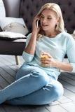 Blonde Dame, die Saftglas hält und pro Telefon spricht Lizenzfreie Stockfotos