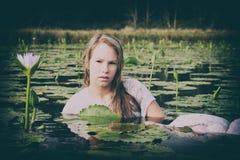 Blonde Dame, die unter die lillies schwimmt Stockfotografie