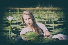 Blonde Dame, die unter die lillies schwimmt Stockfotos