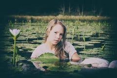 Blonde Dame, die unter die lillies schwimmt Stockfoto