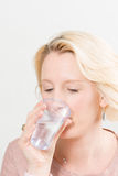 Blonde Dame Drinking Water von einem Plastikschalen-Kopien-Raum Lizenzfreie Stockbilder