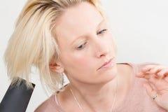 Blonde Dame Drying Her Hair mit elektrischem Schlag-Trockner Stockfotografie