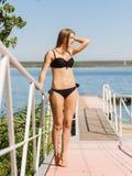 Blonde Dame in einem Bikini gehend auf Pier auf dem Hintergrund des blauen Wassers Seashells gestalten auf Sandhintergrund Stockbild