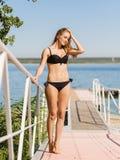 Blonde Dame in einem Bikini gehend auf Pier auf dem Hintergrund des blauen Wassers Seashells gestalten auf Sandhintergrund Lizenzfreies Stockbild