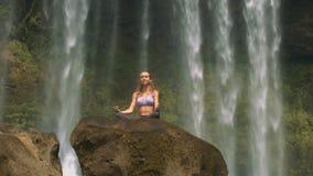 Blonde Dame entspannt sich in der Yogahaltung auf Wasserfallfelsen stock video