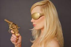 Blonde Dame Holding ein goldenes Gewehr Stockfoto