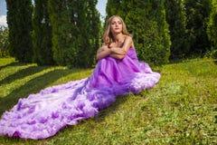 Blonde Dame im rosa Kleid mit dem langen Rock, der weg schaut Stockfotografie