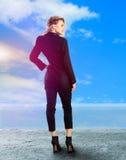 Blonde Dame im schwarzen Anzug auf hohen Absätzen Stockfotos