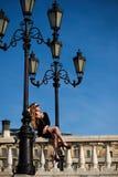 Blonde Dame im schwarzen Kleid, das auf Balustergeländer unter WeinleseStraßenlaterne sitzt Stockfotografie