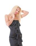 blonde Dame im schwarzen Kleid gegen Weiß Stockfotografie