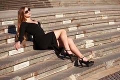 Blonde Dame im schwarzen Kleid mit Decolletage Stockfotos