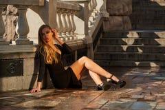Blonde Dame im schwarzen Kleid mit Decolletage Lizenzfreie Stockfotografie