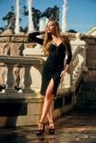 Blonde Dame im schwarzen Kleid mit Decolletage Lizenzfreie Stockbilder