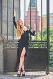 Blonde Dame im schwarzen Kleid mit Decolletage Stockbild
