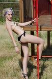 Blonde Dame mit dem tragenden Bikini des dünnen und athletischen Körpers, der Spaß neben einem Spaßpark hat Lizenzfreies Stockfoto