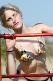 Blonde Dame mit dem tragenden Bikini des dünnen und athletischen Körpers, der Spaß neben einem Spaßpark hat Lizenzfreies Stockbild