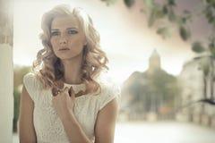 Blonde Dame mit der gelockten Frisuraufstellung im Freien Lizenzfreie Stockfotografie