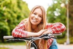 Blonde Dame mit ihrem Fahrrad Lizenzfreie Stockfotos
