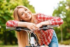 Blonde Dame mit ihrem Fahrrad Stockbilder